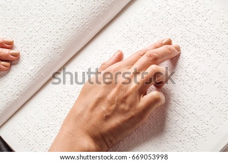 Blind woman read book written in Braille. Close up finger touch to braille Code
