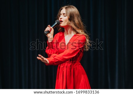 Blind woman sings. Music star performs on stage. Disable girl with microphone in hand. Fashionably dressed lady at opera. Actress doing the show at theatre scene. Attempt of theatrical performance.