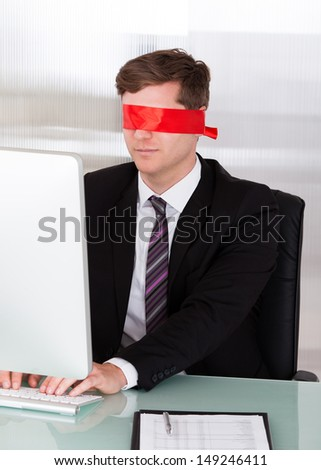 Blindfold businessman at the office working on his computer