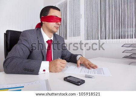 Blindfold businessman at the office working signing a contract