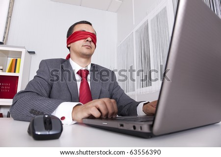 Blindfold businessman at the office working with his laptop