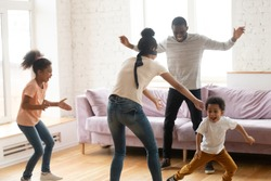 Blindfolded african american mother and happy father with two children playing blind man buff or hide and seek at home in living room. Smiling mum catching dad and little boy and girl.