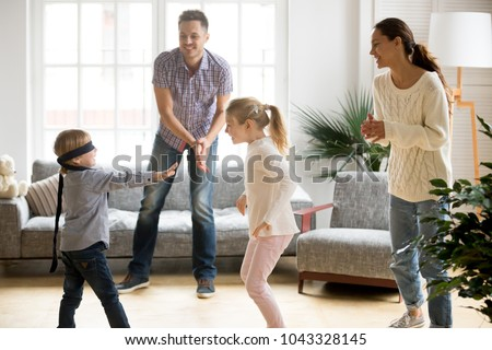 Blindfolded cute little boy playing hide and seek at home, parents and kids laughing spending time together enjoying game on weekend, happy family of four having fun leisure activity in living room