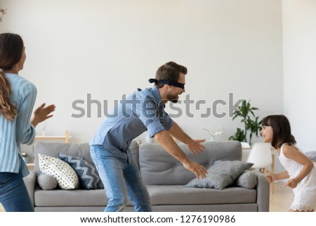 Blindfolded father playing hide and seek game with family at home, cute child daughter runs from dad having fun, parents kid girl laughing spending time together enjoy weekend activity in living room