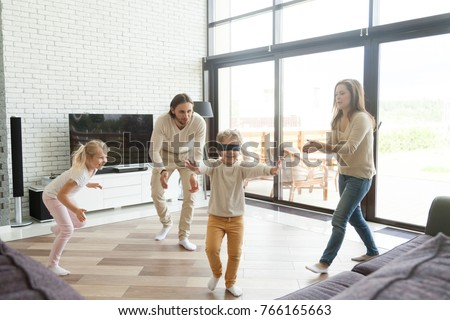 Blindfolded little boy playing hide and seek game at home, happy family of four having fun enjoying leisure activity in living room, parents and kids laughing spending free time together on weekend