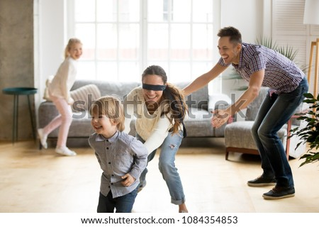 Blindfolded mother catching little son playing hide and seek at home, happy children having fun with mom and dad, parents with kids spending time together in living room, weekend family games concept