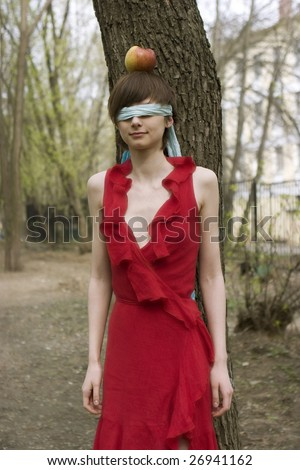 Blindfolded woman eyes. Tied eyes - censorship concept. apple as a target at the head of girl