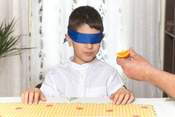 Blindfolded 8 year old boy trying a piece of orange.