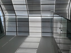 Blinds on ceiling or roof windows. Abstract modern architecture of industrial or office building. Construction industry and minimal architectural design. Geometric pattern of grid or lath structure.