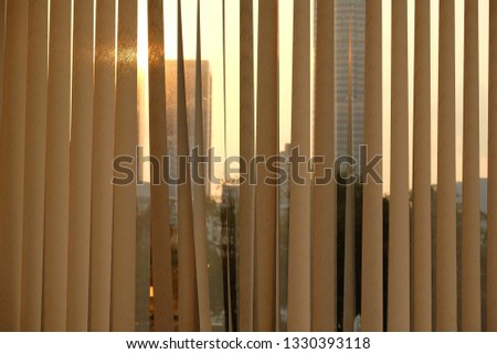 Blinds window decoration,Blinds window decoration of building with sunrise in morning, view of blind with glass surface with silhouette of building in city background  that lighting rising sun #1330393118