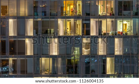 Blinking and flashing windows of the multi-storey building of glass and steel lighting inside and moving people within timelapse. Aerial view of modern residential skyscrapers in Dubai downtown. Pan #1126004135