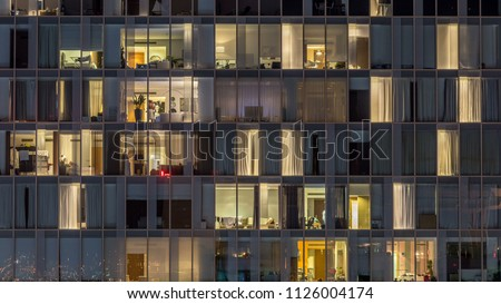 Blinking and flashing windows of the multi-storey building of glass and steel lighting inside and moving people within timelapse. Aerial view of modern residential skyscrapers in Dubai downtown. Zoom