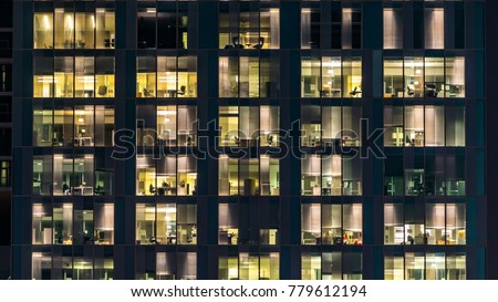Blinking light in window of the multi-storey building of glass and steel lighting and people within timelapse close up view. Dubai, UAE #779612194