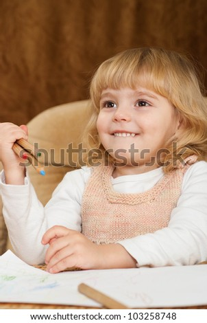 Bliss Caucasian young girl draws a table on a brown background