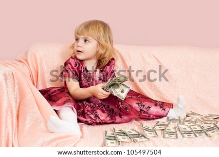 Bliss Caucasian young girl sitting on the couch with the money on an pink background