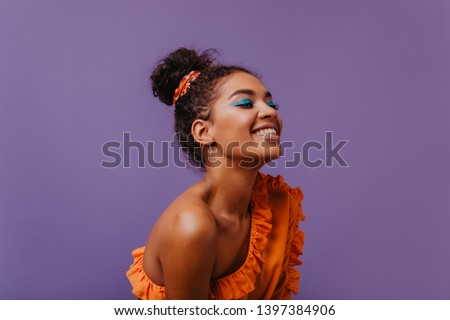 Blissful black woman in summer dress laughing on violet background. Adorable african girl in orange outfit posing with happy face expression.