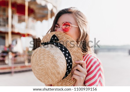 Blissful blonde girl covering face with straw hat while posing in summer day. Outdoor photo of happy young woman in pink sunglasses resting in amusement park.