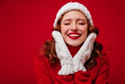Blissful caucasian woman in knitted gloves enjoying christmas. Studio portrait of happy ginger girl with curly hairstyle posing on red background in new year.