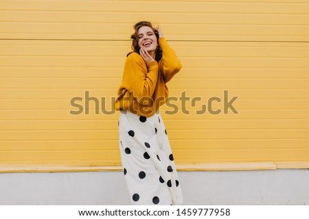 Blissful caucasian woman in trendy white skirt expressing happiness. Glad stylish girl posing on bright yellow background. #1459777958