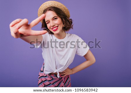 Blissful european girl with dark eyes posing in trendy straw hat. Indoor photo of sensual female model with short hair standing on purple background and laughing. #1096583942