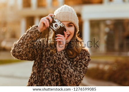 Blissful female model in elegant coat posing with camera. Smiling photographer taking pictures of autumn city.