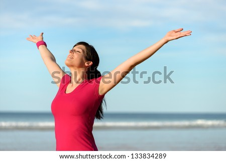 Blissful fitness woman raising arms to the sky on beach at sunset after working out. Happy female athlete feeling the breeze on sea background. Achievements and goals on sport concept.