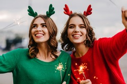 Blissful girls with sparklers having fun outdoor. Photo of two female friends celebrating christmas.