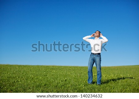 Blissful man enjoying his music outdoors standing in a fresh green field under a sunny blue sky with his head tilted back in pleasure, with copyspace