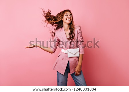 Blissful red-haired girl enjoying studio photoshoot. Carefree caucasian lady in pink jacket laughing on pastel background.