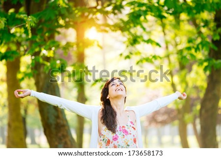 Stock Photo Blissful woman enjoying freedom and life in park on spring.