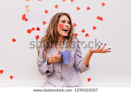 Blissful woman with black manicure enjoying morning. Debonair female model in striped pajamas holding cup of coffee.