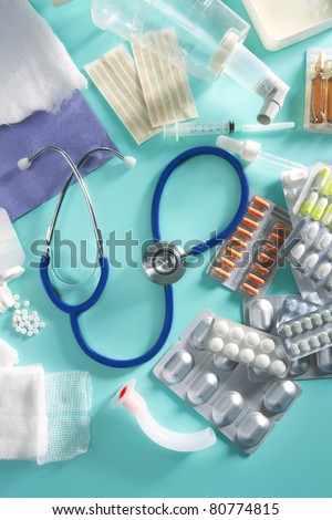 blister of medical pills and pharmaceutical stuff with stethoscope over green background