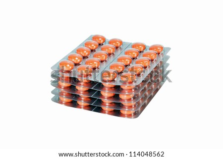 Blisters of orange pills isolated on white