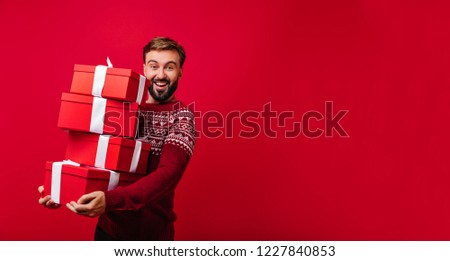 Blithesome bearded white guy enjoying christmas time with presents. Indoor shot of carefree european man in red sweater having fun at new year party.