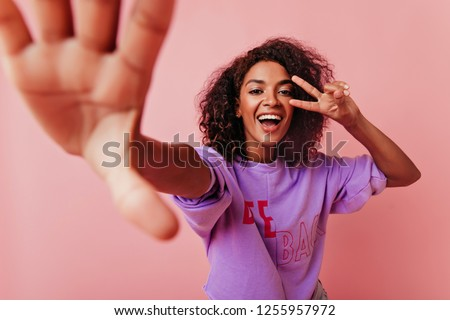 Blithesome black woman with wavy hair making selfie on rosy background. Wonderful girl with positive smile taking picture of herself.