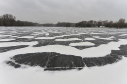 Blizzard and snow storm in the city on a frozen pond. Residential buildings on the banks of the ice-bound river. Covered with ice and snow river in winter. A snowstorm with a strong wind falls on the