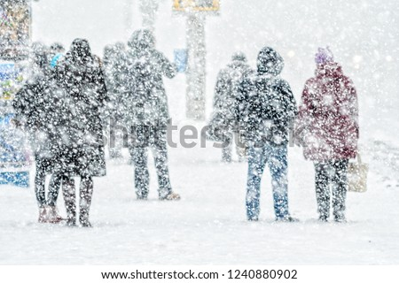 Blizzard in an urban environment. People on bus stop in snowfall. Abstract blurry winter weather background #1240880902