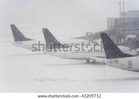 Blizzard on an international airport, airplanes waiting in the snow, free copy space