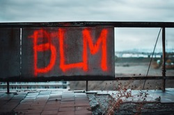 BLM signature painted with acid red paint in the edge of roof