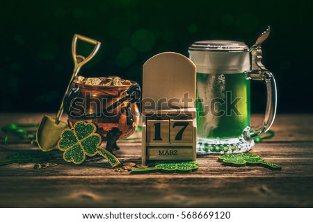 Block calendar for St Patrick's Day, March 17, with green beer and pot of gold, on wooden background.