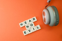 Block letter text on hear no evil and a headphone on orange background.  See no evil, hear no evil, speak no evil concept