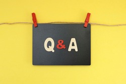 Block letters on Q & A on black chalkboard hanging on rope.  Questions and answers concept