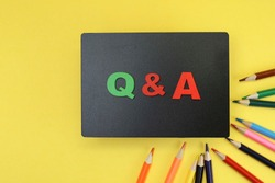 Block letters on Q & A on black plank, questions and answers concept