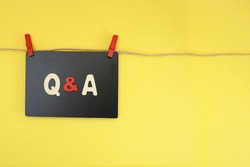 Block letters on Q & A with cloth line and pegs, questions and answers concept