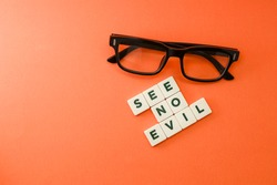 Block letters on see no evil with an eyeglasses isolated on orange background.  See no evil, speak no evil, hear no evil concept