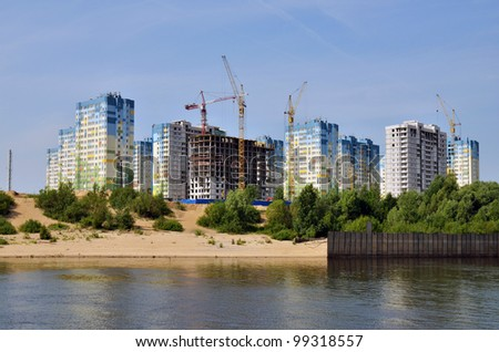 Block of flats and buildings under construction on river bank