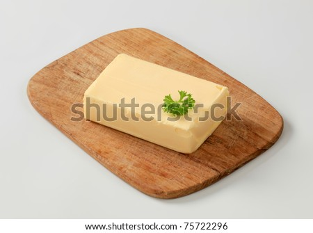 Block of fresh butter  on a cutting board - stock photo