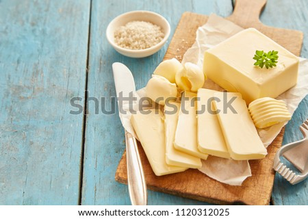 Block of fresh butter sliced on wooden cutting board against blue table #1120312025