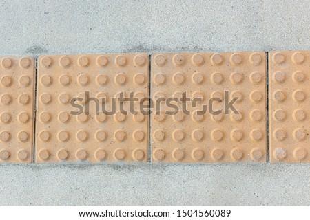 Block tactile paving for blind handicap. Tactile paving for blind handicap on tiles pathway, walkway for blindness people. #1504560089