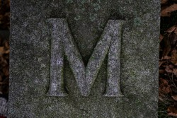 Block with letter M. Embossed on the stone surface or concrete